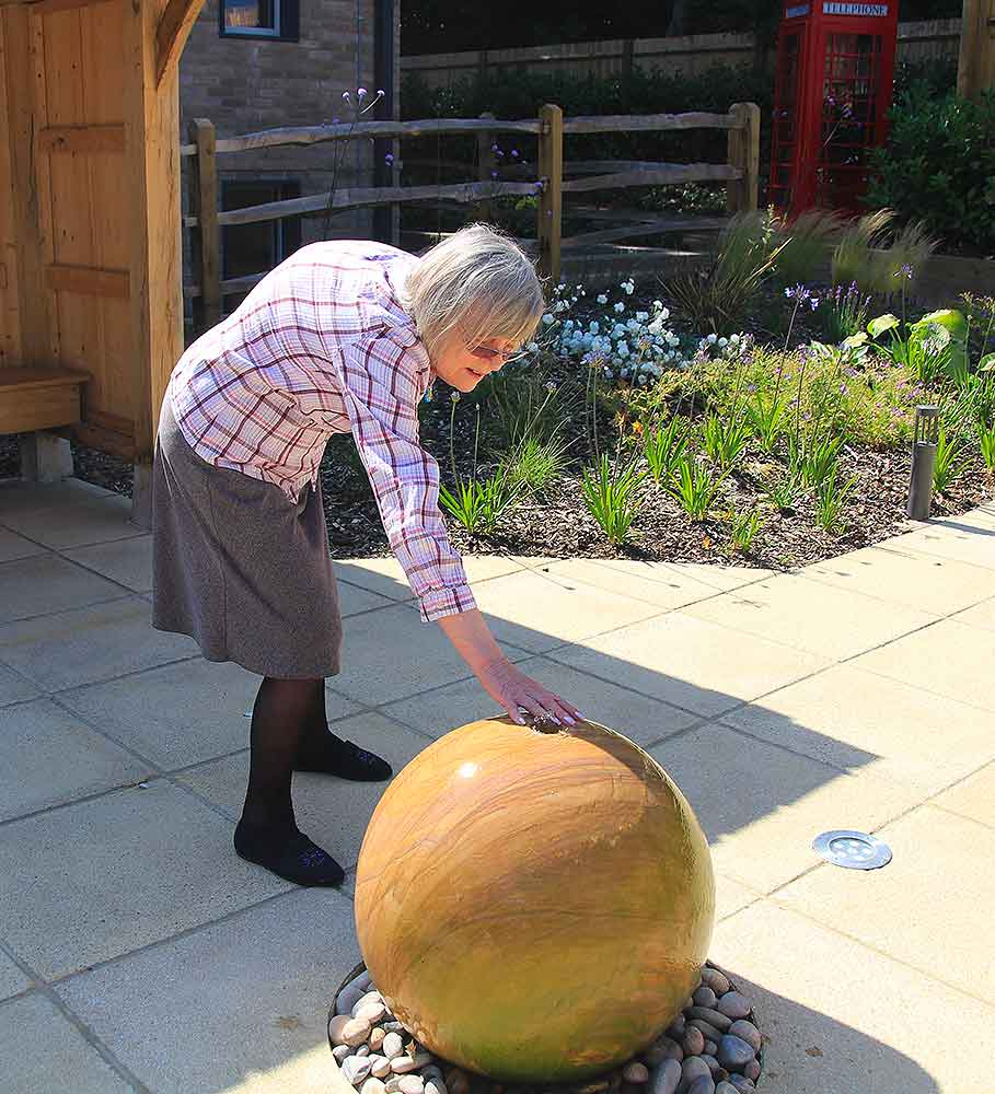 Resident enjoying the water feature, Blatchington Manor residential home, Seaford, East Sussex