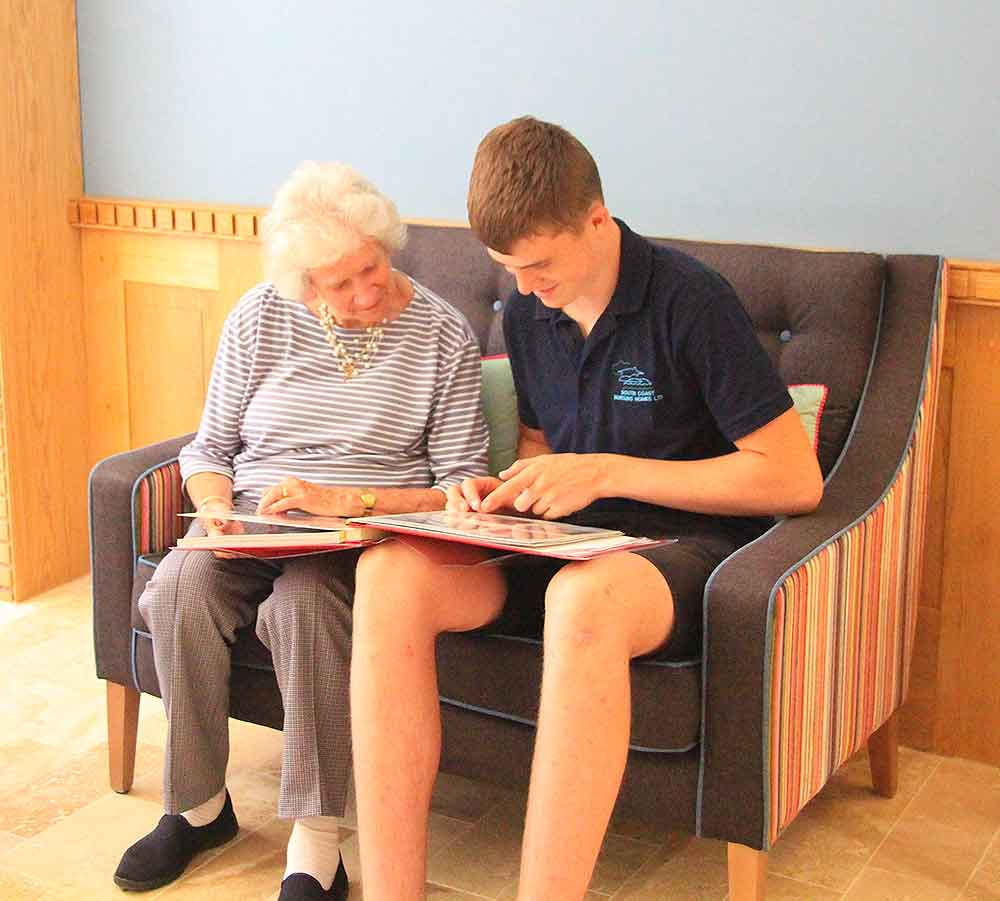 Resident looking at photo album, Blatchington Manor residential home, Seaford, East Sussex